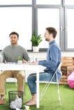 Бизнесмены сидя на таблице и обсуждая новый проект, концепцию сыгранности дела Стоковые Изображения RF