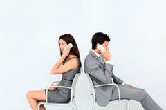 Бизнесмены сидя спина к спине говорить на телефоне Стоковое Фото