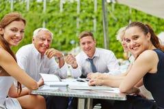 Бизнесмены сидя outdoors на таблице Стоковая Фотография RF