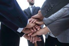Бизнесмены складывая их руки совместно стоковая фотография