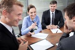 Бизнесмены смеясь над во время деловой встречи стоковые изображения