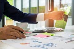 Бизнесмены смотрят диаграмму сальто на экране компьтер-книжки, держат ручку i Стоковые Фото