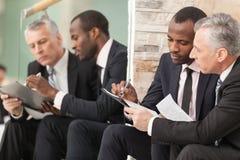 Бизнесмены смотря бумагу Стоковое Изображение RF