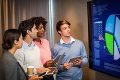 Бизнесмены смотря диаграмму в конференц-зале Стоковое Изображение