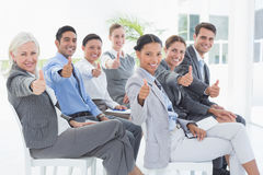 Бизнесмены смотря камеру с большими пальцами руки вверх Стоковое Изображение RF
