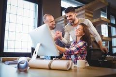 Бизнесмены смотря компьютер в творческом офисе Стоковая Фотография RF
