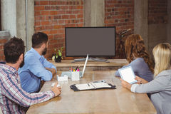 Бизнесмены смотря к экрану пока сидящ в офисе Стоковая Фотография