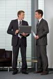 Бизнесмены смотря один другого в офисе Стоковые Изображения