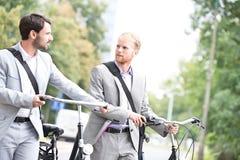 Бизнесмены смотря один другого пока держать bicycles outdoors Стоковое фото RF