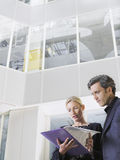 2 бизнесмены смотря папку в офисе Стоковое Изображение