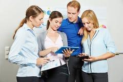 Бизнесмены смотря планшет в офисе Стоковое фото RF