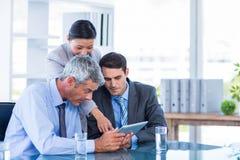 Бизнесмены смотря планшет Стоковое Изображение