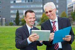 Бизнесмены смотря таблетку Стоковое Изображение RF