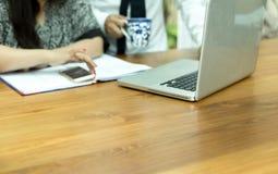 Бизнесмены смотря тетрадь компьютера обсуждая проект Стоковое фото RF