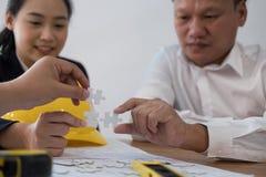 Бизнесмены собирая часть головоломки совместно работник t co Стоковая Фотография