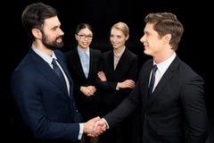 Бизнесмены соединяя и тряся руки пока коммерсантки смотря на их изолировали на черноте Стоковое фото RF