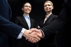 Бизнесмены соединяя и тряся руки пока коммерсантки смотря на их изолировали на черноте Стоковые Фотографии RF