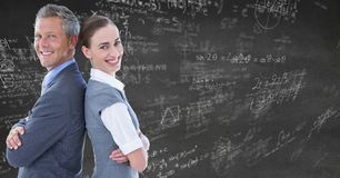 Бизнесмены спина к спине против серой стены с математикой doodles Стоковые Изображения