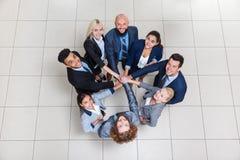 Бизнесмены стойки группы в круге, команде предпринимателей кладя их стог рук смотрят вверх сотрудничество сыгранности Стоковая Фотография RF