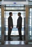 Бизнесмены стоя лицом к лицу в лифте Стоковые Фотографии RF