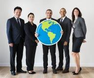 Бизнесмены стоя и держа значок глобуса Стоковая Фотография