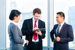 Бизнесмены стоя на деятельности окна офиса Стоковая Фотография