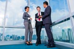 Бизнесмены стоя на деятельности окна офиса Стоковая Фотография RF