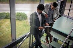 Бизнесмены стоя на лестницах Бизнесмены имея conv Стоковые Изображения RF