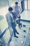 Бизнесмены стоя на лестницах Бизнесмены имея conv Стоковая Фотография