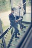 Бизнесмены стоя на лестницах Бизнесмены имея conv Стоковые Фото