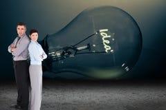 Бизнесмены стоя перед электрической лампочкой Стоковое фото RF
