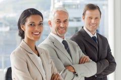 3 бизнесмены стоя при их пересеченные оружия Стоковая Фотография