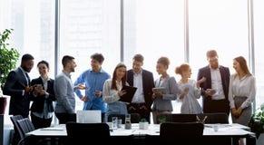 Бизнесмены стоя против окна, обсуждая работу стоковое изображение
