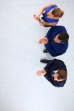 Бизнесмены стоя совместно и хлопая - topview Стоковое Изображение
