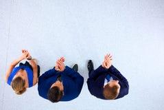 Бизнесмены стоя совместно и хлопая - topview Стоковые Фото