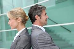 Бизнесмены стоя спина к спине и усмехаясь Стоковое фото RF