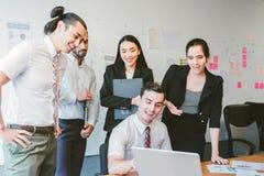 Бизнесмены счастливые в современном офисе с компьтер-книжкой Стоковые Фото