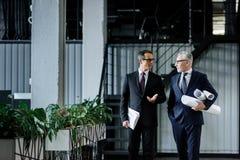 бизнесмены с блокнотом и светокопии имея переговор стоковое фото rf