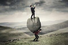 Бизнесмены с валуном в холме Стоковая Фотография