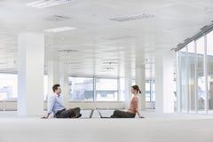 Бизнесмены с компьтер-книжками в пустых размерах офиса Стоковая Фотография
