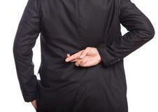 Бизнесмены с одной рукой на карманн и другим при пересеченные пальцы Стоковая Фотография