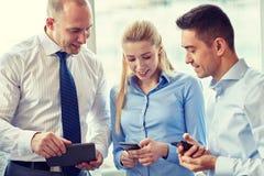 Бизнесмены с ПК и smartphones таблетки Стоковое Изображение