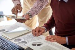 Бизнесмены с ПК таблетки и диаграммы на офисе Стоковые Изображения RF