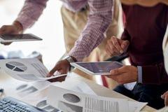 Бизнесмены с ПК таблетки и диаграммы на офисе Стоковые Фотографии RF