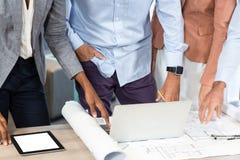 Бизнесмены с светокопией на столе используя компьтер-книжку Стоковое фото RF