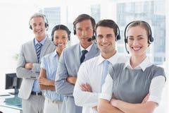 Бизнесмены с шлемофонами усмехаясь на камере Стоковые Фото