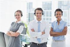 Бизнесмены с шлемофонами усмехаясь на камере Стоковое Фото