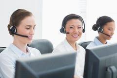 Бизнесмены с шлемофонами усмехаясь на камере Стоковая Фотография RF