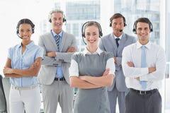 Бизнесмены с шлемофонами усмехаясь на камере Стоковые Изображения