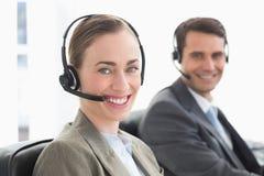 Бизнесмены с шлемофонами усмехаясь на камере Стоковая Фотография